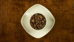 Coffee cup filled with beans stop motion animation turning clockwise topview. Coffee cup filled with beans stop motion animation turning clockwise top view stock video footage