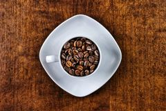 Coffee cup filled with coffee beans topview. Coffee cup filled with coffee beans top view Royalty Free Stock Photo