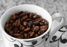 Coffee cup filled with coffee beans Stock Photo