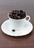 Coffee cup filled with coffee beans. White porcelain coffee cup filled with coffee beans Stock Images