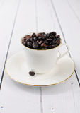 Coffee cup filled with coffee beans. On white wooden background Stock Photography