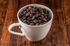 Coffee Cup filled with Coffee Beans at Breakfast Table Stock Photography