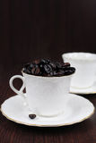 Coffee cup filled with coffee beans on dark backgr Royalty Free Stock Photo