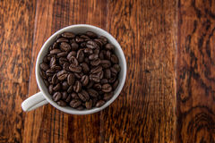 Coffee Cup filled with Coffee Beans on Wood Table Royalty Free Stock Photo