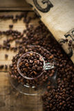 Coffee cup filled with coffee beans. On wooden background royalty free stock image