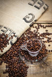 Coffee cup filled with coffee beans. On wooden background stock photo