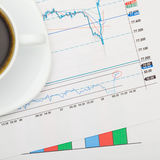 Coffee cup and financial charts - close up shot Royalty Free Stock Photography