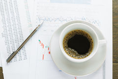 Coffee cup and financial documents on table Stock Photos