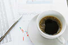 Coffee cup and financial documents on table Stock Photo
