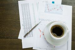 Coffee cup and financial documents on table Royalty Free Stock Photo