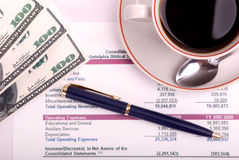 Coffee cup and financial report. Top view of money,pen,coffee cup and financial report Royalty Free Stock Image