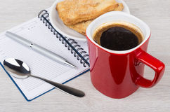 Coffee cup, flaky cookies, notepad and pen on table Royalty Free Stock Image