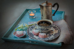 Coffee cup with flower and burning candle Royalty Free Stock Photo