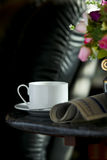 Coffee cup with flower and newspaper. Morning coffee cup with flower and newspaper -- light from window -- focus on the cup royalty free stock photos