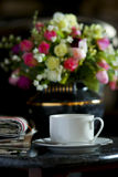 Coffee cup with flower and newspaper. Morning coffee cup with flower and newspaper -- light from window -- focus on the cup stock images