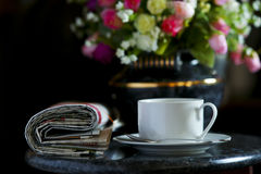 Coffee cup with flower and newspaper. Morning coffee cup with flower and newspaper -- light from window -- focus on the cup stock photography