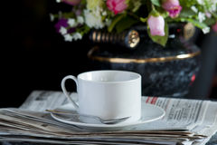 Coffee cup with flower and newspaper. Morning coffee cup with flower and newspaper -- light from window -- focus on the cup royalty free stock photo