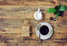 Coffee cup, flower pot, milk jug, gift box on wooden table Stock Image