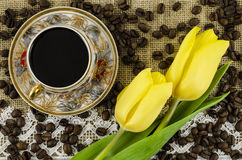 Coffee cup with flowers and coffee beans on linen background Stock Image