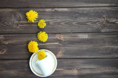 Coffee Cup and flowers of dandelions. On a wooden table Royalty Free Stock Photography