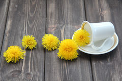 Coffee Cup and flowers of dandelions. On a wooden table Stock Photos