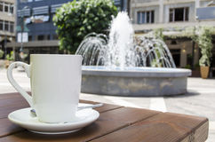 Coffee cup and fountain background. Coffee cup on table and fountain background Stock Image