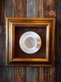 Coffee cup in a frame hanged on a wall in a moder art demo Royalty Free Stock Photo