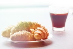 Coffee cup and fresh baked croissants on wooden background. Top view , light toning. Coffee cup and fresh baked croissants on wooden background. Top View Stock Image