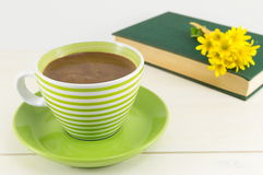 Coffee cup with fresh flowers and a book Stock Photography