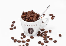 Coffee cup full of beans and spoon. Espresso cup full of coffee beans with a spoon on white background Royalty Free Stock Images
