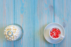 Coffee cup full of candies flat lay on rustic light blue wooden background Royalty Free Stock Photography