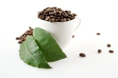 Coffee cup full of coffee beans Stock Photos