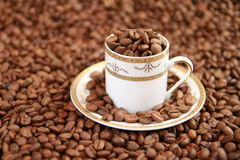 Coffee cup full of coffee beans Stock Photo