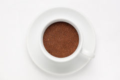 Coffee cup full of ground coffee on soucer against white background, top view Royalty Free Stock Images