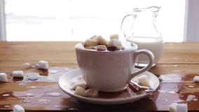 Coffee cup full of lump sugar on wooden table. Unhealthy eating, diabetes, object and drinks concept - coffee cup full of lump sugar on wooden table with cream stock video