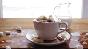 Coffee cup full of lump sugar on wooden table. Unhealthy eating, diabetes, object and drinks concept - coffee cup full of lump sugar on wooden table with cream stock footage