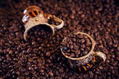 Coffee cup full of roasted coffee beans. Stock Photos