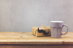 Coffee cup and gift box on wooden table. Father's day holiday Royalty Free Stock Photo