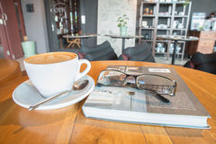 Coffee cup with glassware on book on table Royalty Free Stock Photos
