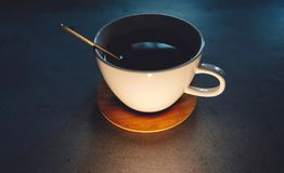 coffee cup with golden spoon and wooden saucer on concrete table stock images