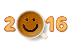Coffee cup for good mood in New Year 2016. Coffee cup with funny smiling face on frothy surface and cookies in shape of digits are forming together the number Stock Image