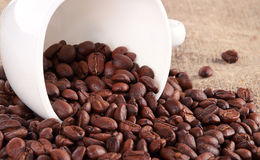 Coffee cup and grain on background Royalty Free Stock Image