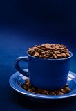 Coffee cup with grains on a dark blue background Royalty Free Stock Image