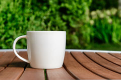 Coffee cup in green garden on table Royalty Free Stock Images