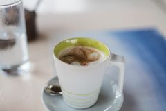 A coffee cup with a green rim Royalty Free Stock Images