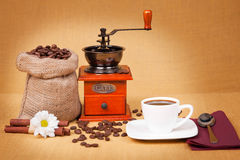 Coffee cup with grinder and burlap sack of roasted Stock Images