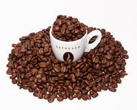Coffee cup and grouped beans. Espresso cup and coffee beans grouped together on white background Stock Photo