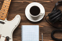 Coffee cup and guitar on wooden table. A cup of coffee, a guitar, headphones and a notebook on a dark wooden board. Top view Stock Image