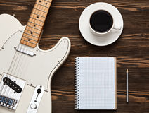 Coffee cup and guitar on wooden table. A cup of coffee, a guitar and a notebook on a dark wooden board Stock Photos