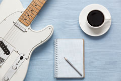 Coffee cup and guitar on wooden table. A cup of coffee, a guitar and a notebook on a light wooden board Royalty Free Stock Photo